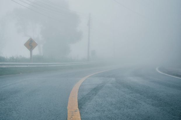foggy rural asphalt highway perspective with white line, misty road, Road with traffic and heavy fog, bad weather driving